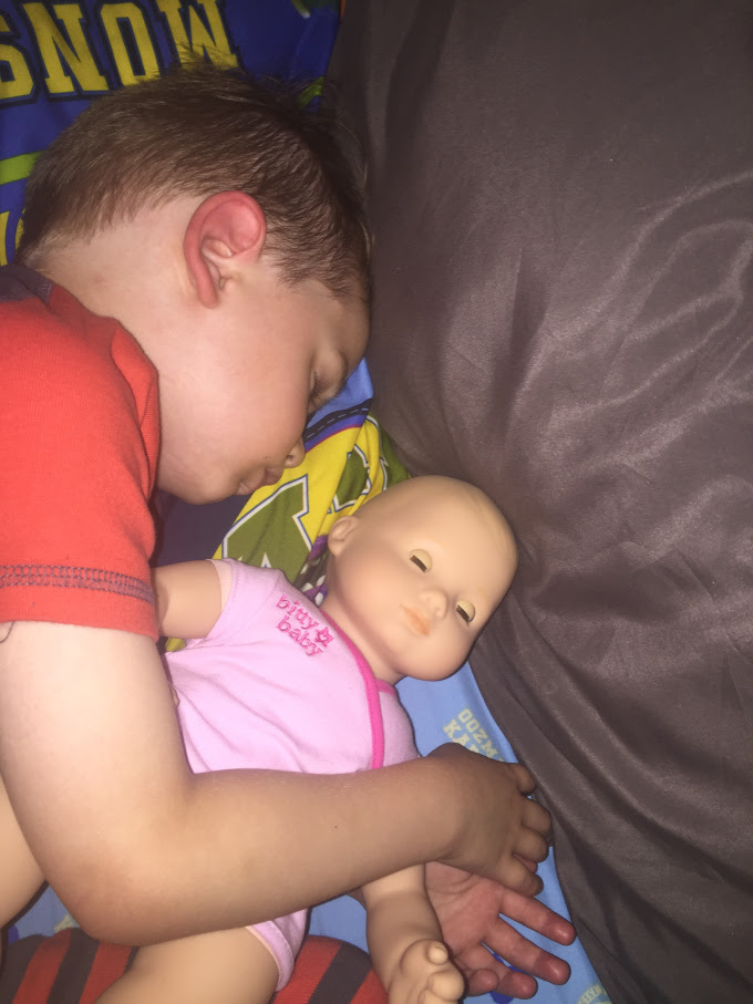 boy sleeping with his american girl doll