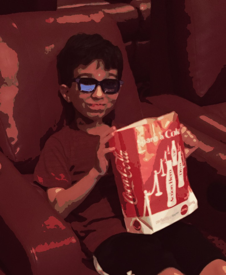 little boy with popcorn in lap at the movies
