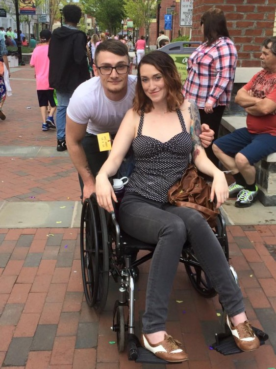 woman in wheelchair with man standing behind