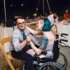 woman in wheelchair dancing with husband sitting in chair