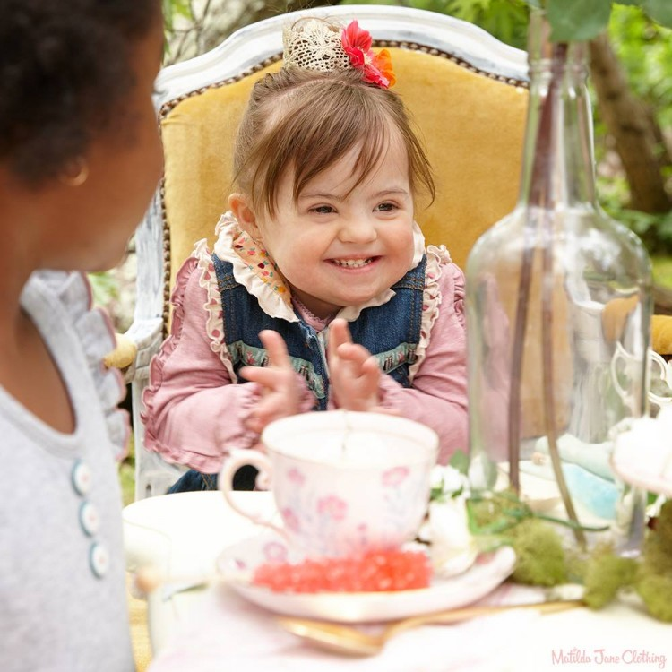 Young girl sitting at table, modeling for Matilda Jane Clothing