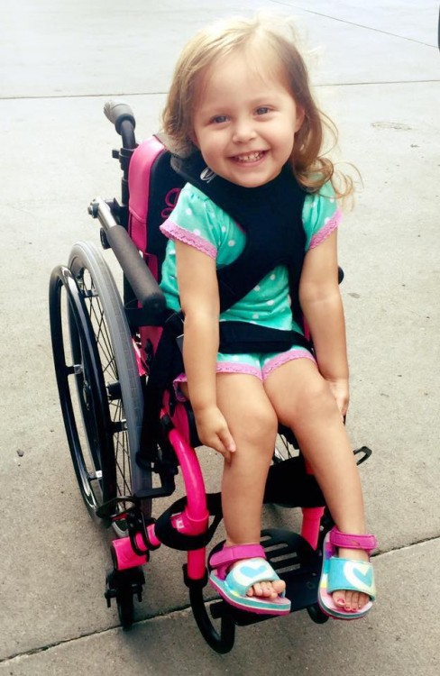 Kelsy's daughter with SMA in a pink wheelchair