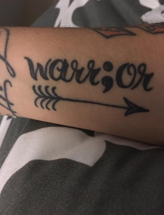 "tattoo reads ""warrior"""