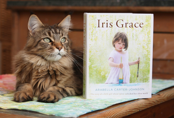 "Thula the cat poses with a copy of Arabella Carter-Johnson's new book ""Iris Grace."""