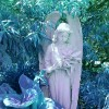 small angel statue holding flowers in a garden