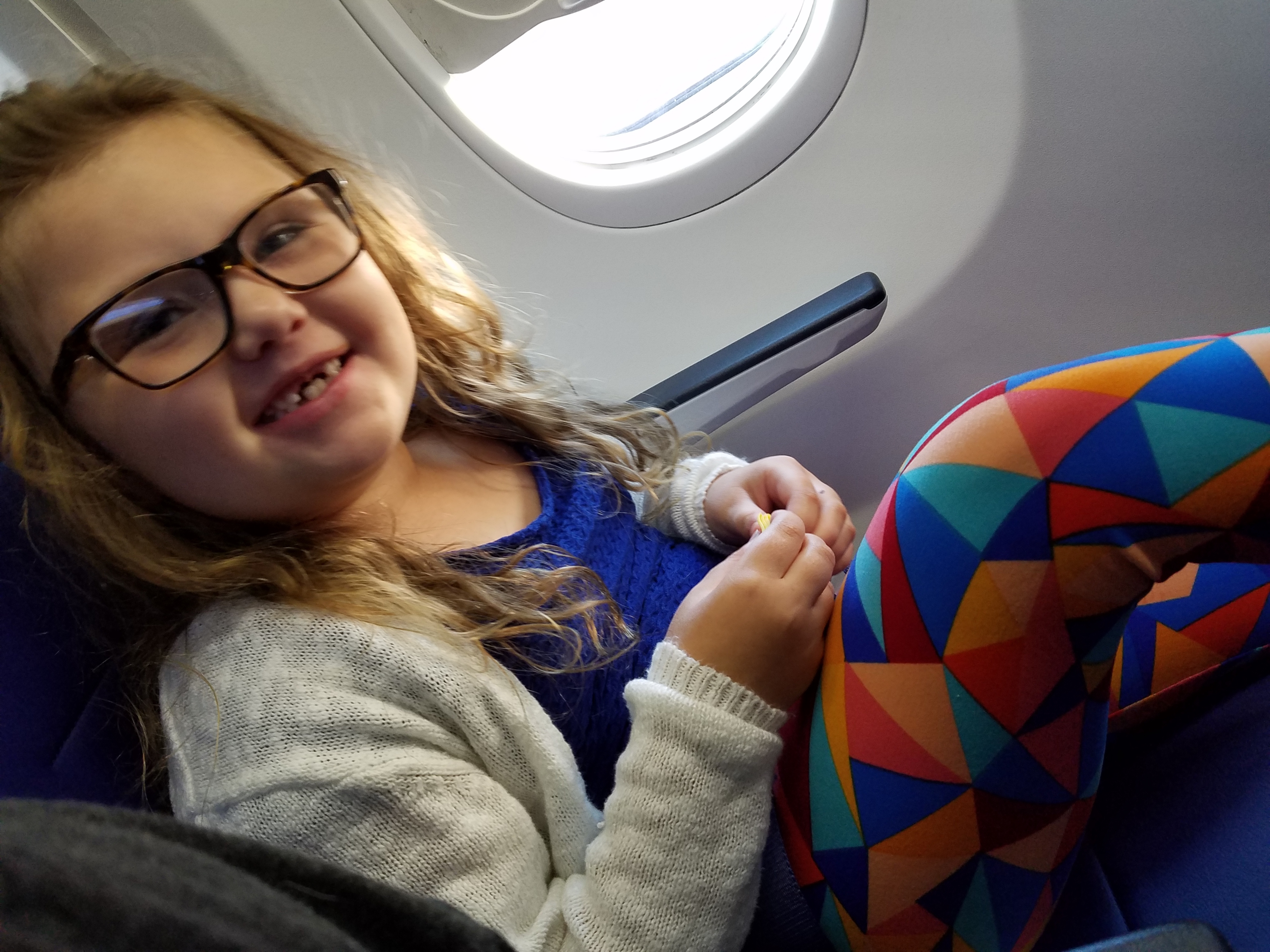 krystle's daughter in the window seat of the plane