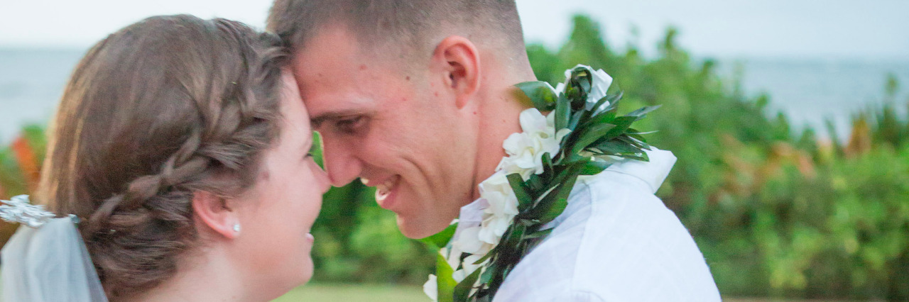 A couple on their wedding day, embracing eye to eye.