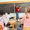 teacher pointing to blackboard in class