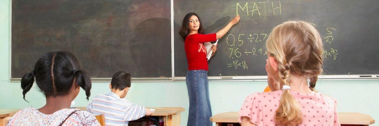 teacher pointing to blackboard in class