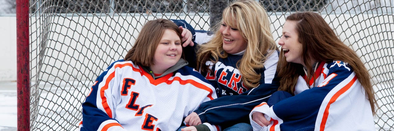A mom and her two daughter sit on a hockey rink, smiling and laughing