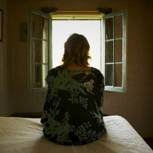 Woman sitting on bed looking out window