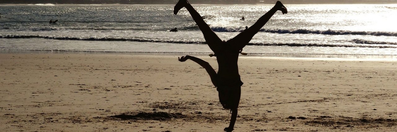 Person doing a cartwheel on the beach with the sun setting in the background