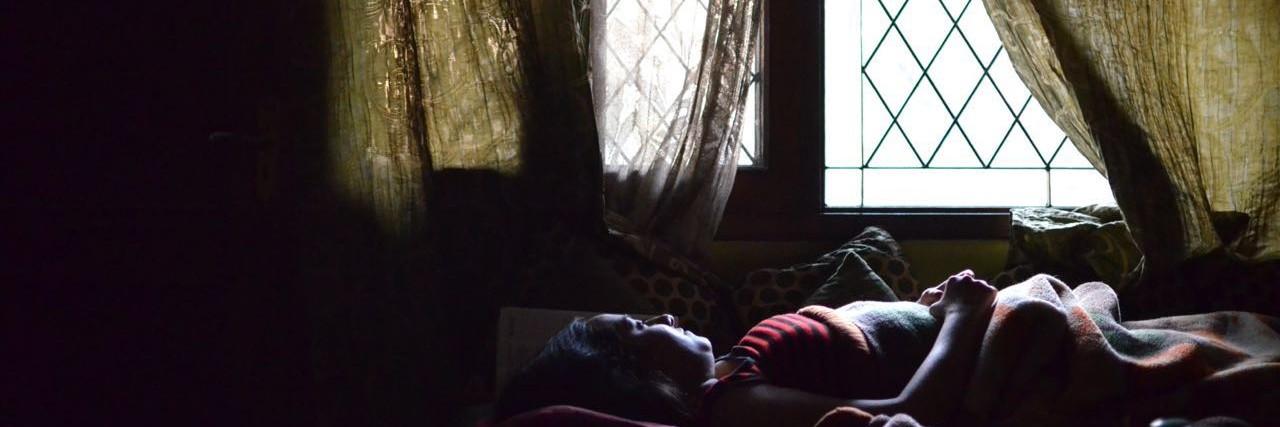 woman laying on bed near window