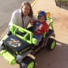 Arshaan with his physical therapist in a jeep she made outside
