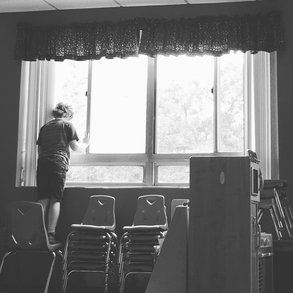 little boy with autism at school near the window