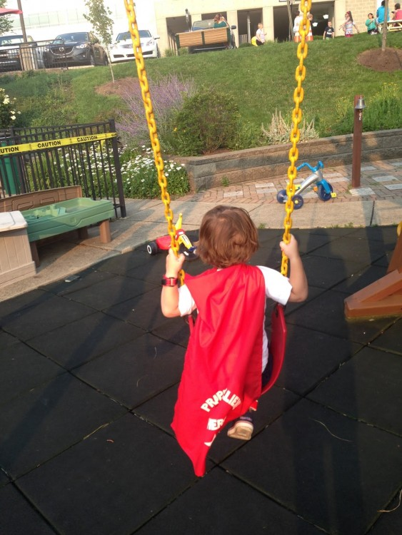 Cohen on a swing, wearing his superhero cape.