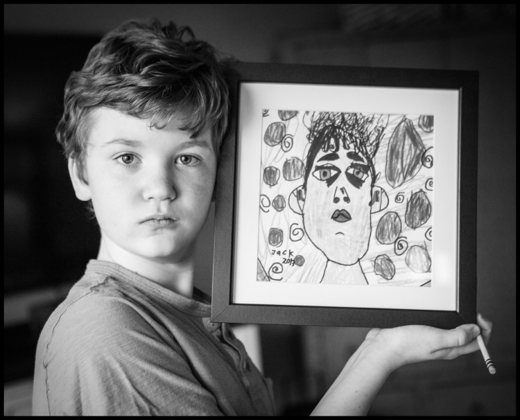 Photograph of a boy, Jack, holding up a drawing