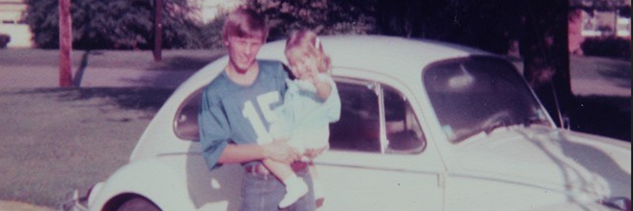A man holding his daughter in front of car