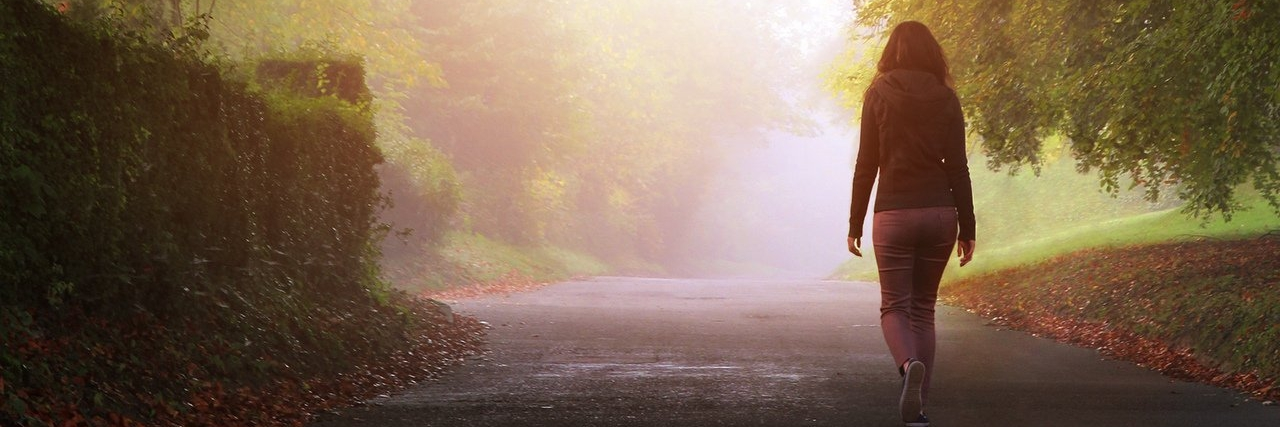 woman walking alone on a misty day