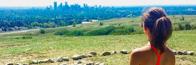 Woman overlooking a city skyline from a hill with her dog next to her