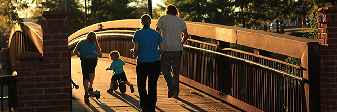 Family walking across a bridge.