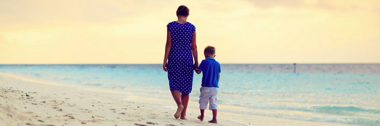 mother and son walking on the beach