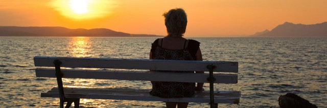 woman sitting on a bench and watching the sunset