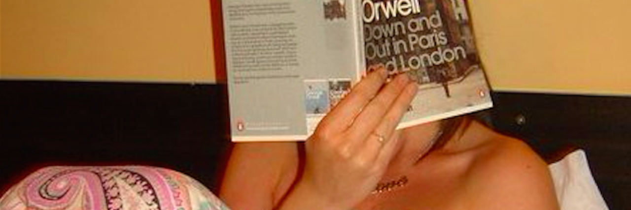 the author holding a book in front of her face