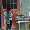 "Woman holding baby in front of wooden door and sign that says ""Happily ever after starts here."""