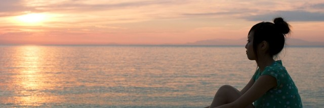 woman sitting looking and sunset over ocean