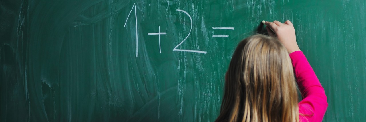 female student answering a math question on a chalk board