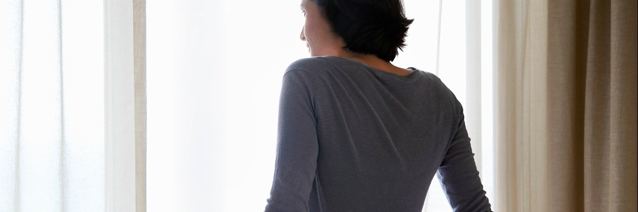 Woman looking through window, sitting on bed, back view
