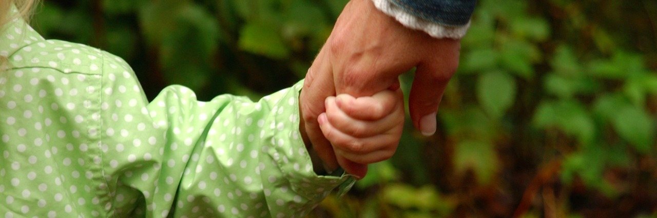 Parent holding child's hand in park