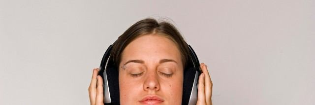 Young woman listening to music on headphones.