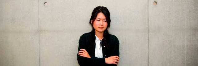 A woman with her arms crossed, looking to the side while leaning against a cement wall