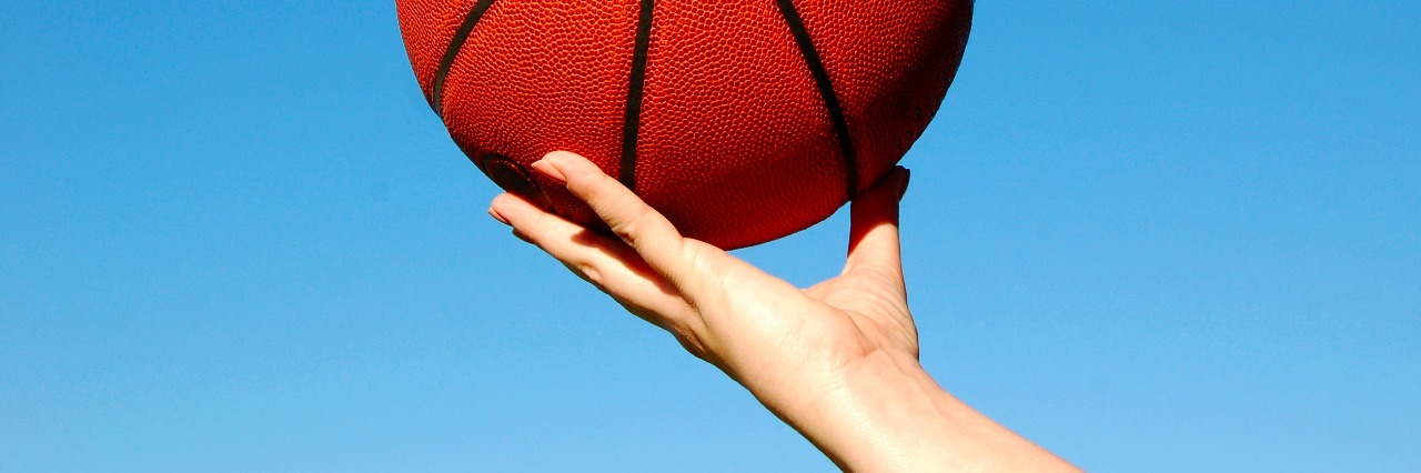 basketball being held in hand against a brilliant blue sky