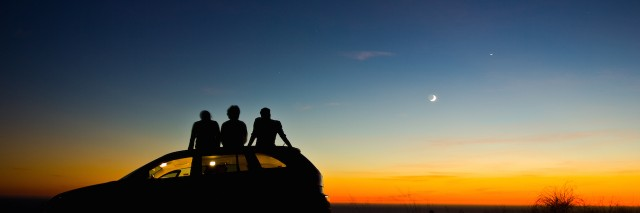 three friends sitting on their car at sunset