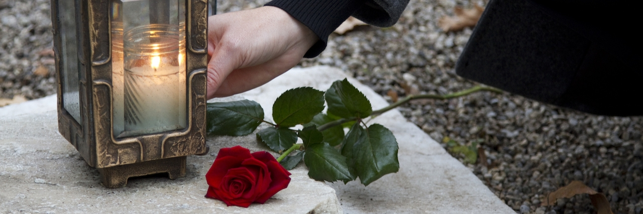 Woman lighting a candle next to a rose
