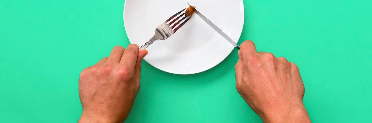 Knife and fork cutting into small meal on a plate