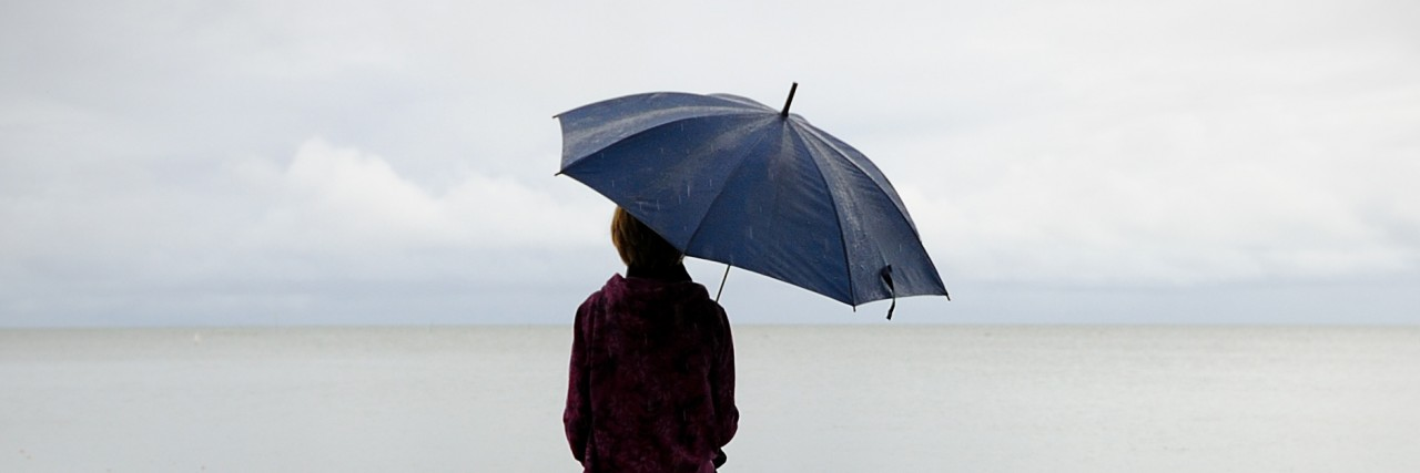 A person sitting on a dock, holding an umbrella on an overcast day
