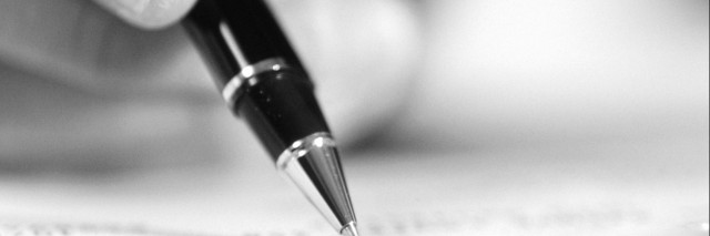 Black and white photo of person holding a pen
