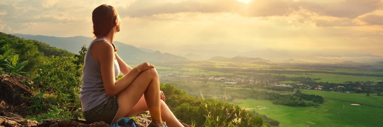 Girl sits on the edge of cliff and looking at sun valley and mountains