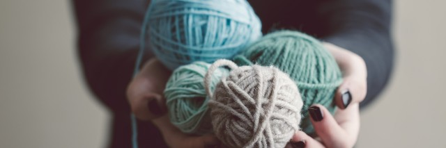 Hands holding balls of yarn
