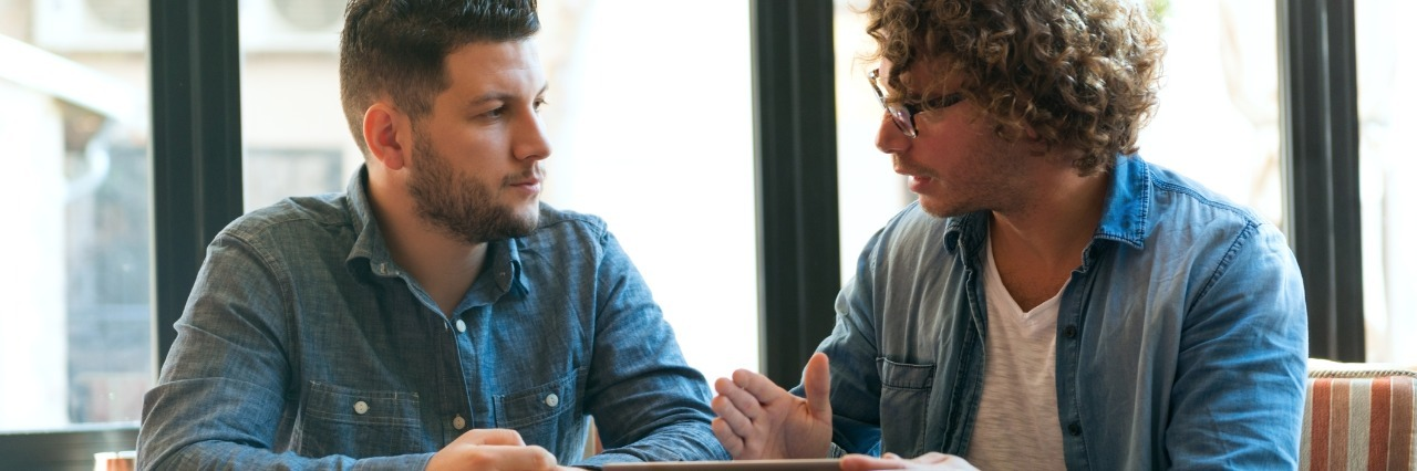 two young men chatting in a cafe