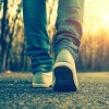 Close-up of someone wearing sneakers and a pair of jeans, walking down a tree-lined path at sunset