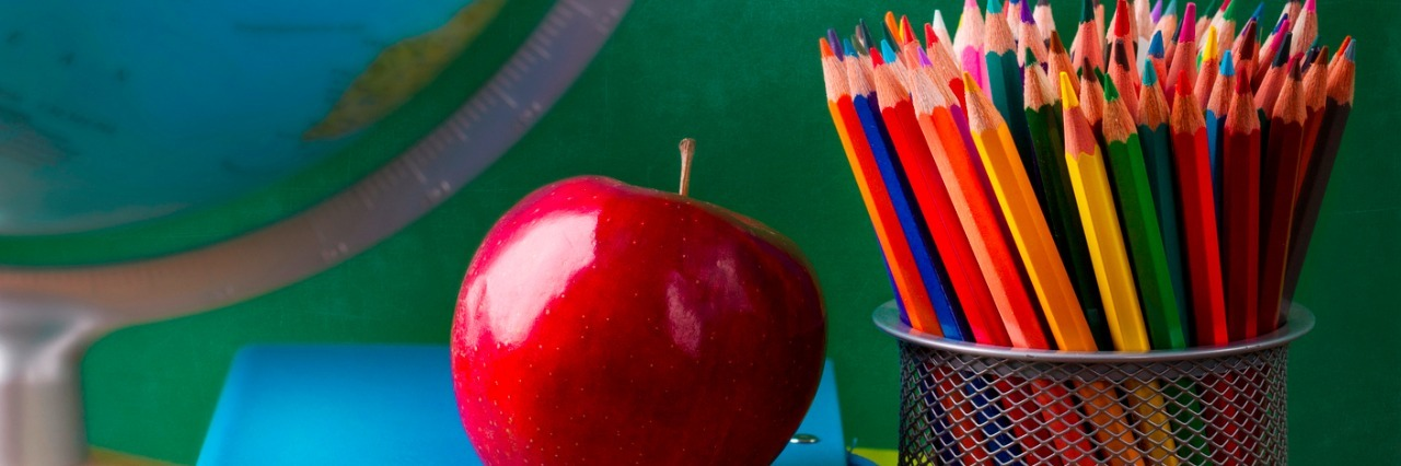 Stack of books, red apple, globe and pencils