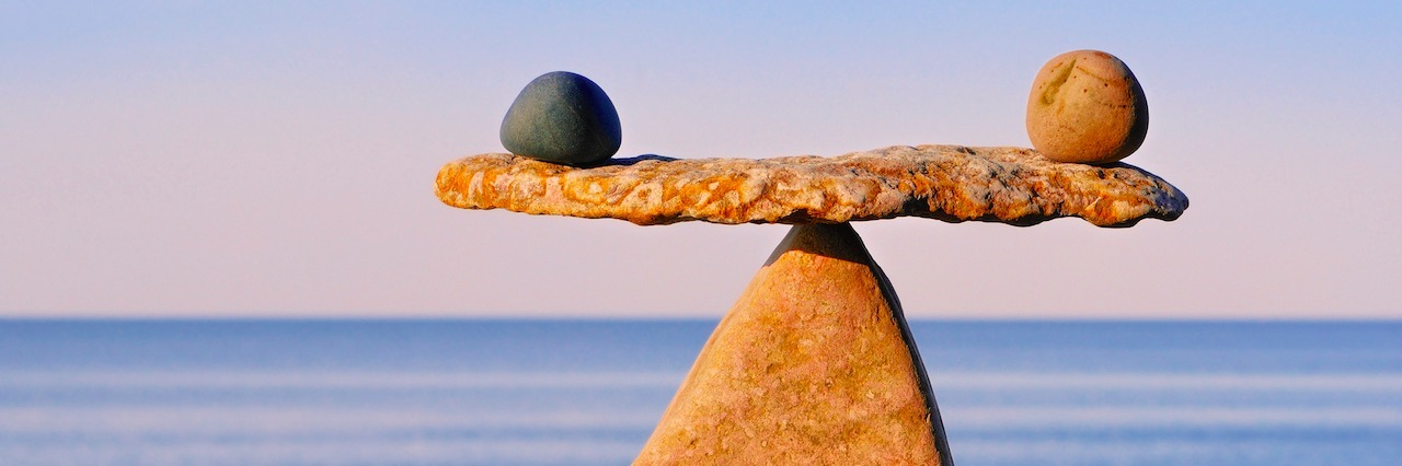 two rocks balancing on a rock scale