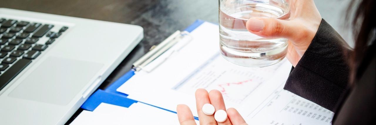 Business people taking aspirin in office