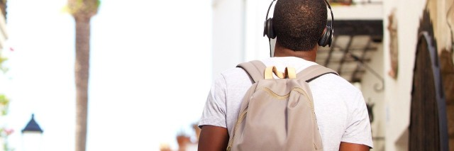 Rear view of man with backpack wearing headphones and walking