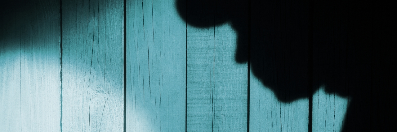 Unrecognizable burglar with flashlight in shadow on wood background, with space for text or image